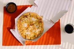 Äta lunch tid, pizza i en öppen ask på tabellen arkivbild