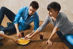Äta mat Grupp av vänner som äter snabbmat som dricker sodavatten royaltyfri foto