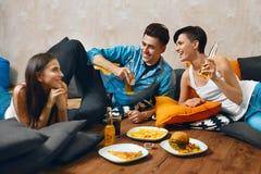 Äta mat Grupp av vänner som äter snabbmat som dricker sodavatten arkivbild