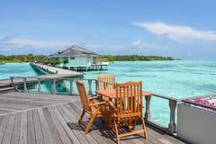 Äta middag aktivering med trätabeller och stolar på restaurangen nära havet på Maldiverna Fotografering för Bildbyråer