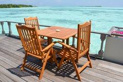 Äta middag aktivering med trätabeller och stolar på restaurangen nära havet på semesterorten Royaltyfri Bild