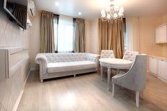 Äta middag område med soffan och TV Ljust rum i beiga, guld- färg Arkivfoton