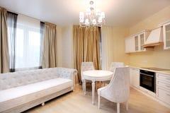 Äta middag område med soffan Vitt kök i beige färg arkivfoto