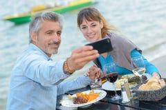 Äta middag par som tar självståendefotografiet royaltyfria bilder