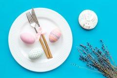 Äta middag tabell för påsk i pastellfärgade färger Platta, bestick, målade ägg-, pepparkaka- och lavendelfilialer på blå bakgrund royaltyfria bilder