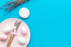 Äta middag tabell för påsk i pastellfärgade färger Platta, bestick, målade ägg-, pepparkaka- och lavendelfilialer på blå bakgrund fotografering för bildbyråer