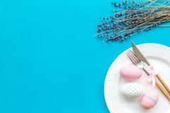 Äta middag tabell för påsk i pastellfärgade färger Platta, bestick, målade ägg-, pepparkaka- och lavendelfilialer på blå bakgrund arkivfoto