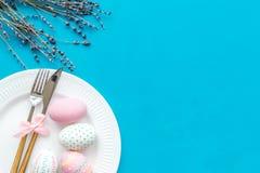 Äta middag tabell för påsk i pastellfärgade färger Platta, bestick, målade ägg-, pepparkaka- och lavendelfilialer på blå bakgrund arkivbilder