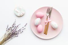 Äta middag tabell för påsk i pastellfärgade färger Platta, bestick, målade ägg-, pepparkaka- och lavendelfilialer på vit royaltyfria foton