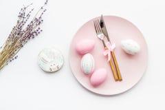 Äta middag tabell för påsk i pastellfärgade färger Platta, bestick, målade ägg-, pepparkaka- och lavendelfilialer på vit royaltyfri bild