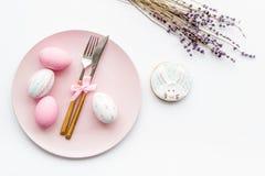 Äta middag tabell för påsk i pastellfärgade färger Platta, bestick, målade ägg-, pepparkaka- och lavendelfilialer på vit royaltyfri fotografi
