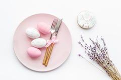 Äta middag tabell för påsk i pastellfärgade färger Platta, bestick, målade ägg-, pepparkaka- och lavendelfilialer på vit fotografering för bildbyråer