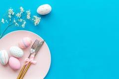 Äta middag tabell för påsk i pastellfärgade färger Platta, bestick, målade ägg, pepparkaka och torr blommafilial på blå bakgrund royaltyfri fotografi