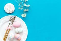 Äta middag tabell för påsk i pastellfärgade färger Platta, bestick, målade ägg, pepparkaka och torr blommafilial på blå bakgrund royaltyfri bild