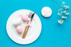 Äta middag tabell för påsk i pastellfärgade färger Platta, bestick, målade ägg, pepparkaka och torr blommafilial på blå bakgrund arkivbild
