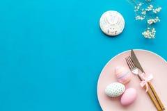 Äta middag tabell för påsk i pastellfärgade färger Platta, bestick, målade ägg, pepparkaka och torr blommafilial på blå bakgrund arkivbilder