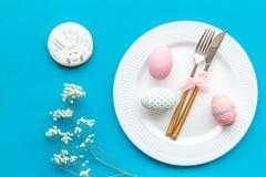 Äta middag tabell för påsk i pastellfärgade färger Platta, bestick, målade ägg, pepparkaka och torr blommafilial på blå bakgrund royaltyfri foto