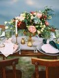 Äta middag tabell med blom- den utomhus- garnering och festliga tabellinställningen arkivbild