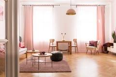 Äta middag tabell med stol i mitt av ljus pastellfärgad rosa vardagsrum i hyreshus royaltyfria bilder