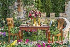 Äta middag tabellen i blommaträdgård royaltyfri fotografi