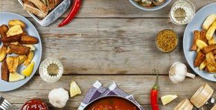 Äta middag tabellen med en variation av mål och mellanmål Köttbullar bakade potatiskilar, kött, champinjoner, ketchup Lantlig sti Arkivfoton