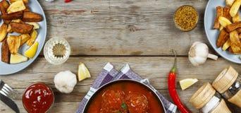 Äta middag tabellen med en variation av mål och mellanmål Köttbullar bakade potatiskilar, kött, champinjoner, ketchup Lantlig sti Royaltyfria Foton