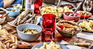 Äta middag tabellen med en variation av mellanmål och sallader Lax oliv, vin, grönsaker, grillat fiskrostat bröd begreppet av en  royaltyfri foto