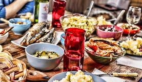 Äta middag tabellen med en variation av mellanmål och sallader Lax oliv, vin, grönsaker, grillat fiskrostat bröd begreppet av en  royaltyfri bild
