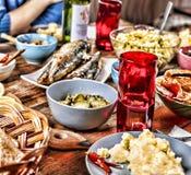 Äta middag tabellen med en variation av mellanmål och sallader Lax oliv, vin, grönsaker, grillat fiskrostat bröd begreppet av en  arkivfoto