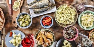 Äta middag tabellen med en variation av mellanmål och sallader Lax oliv, vin, grönsaker, grillat fiskrostat bröd begreppet av en  royaltyfri fotografi