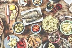 Äta middag tabellen med en variation av mellanmål och sallader Lax oliv, vin, grönsaker, grillat fiskrostat bröd begreppet av en  fotografering för bildbyråer