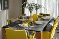 Äta middag tabellen och bekväma stolar i modernt hem Fotografering för Bildbyråer