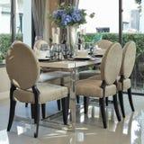 Äta middag tabellen och bekväma stolar med den eleganta tabellinställningen Arkivbilder