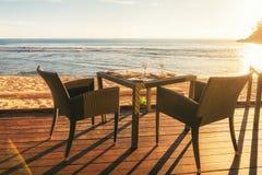 Äta middag tabellen och två stolar på att pryda av havssidan på aftonen su Arkivbilder