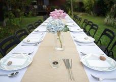 Äta middag uppsättningen på det vita tabellarket med härliga den utomhus- bukettblomman arkivbild