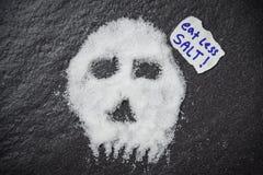 Äta mindre saltar för vård- begrepp/hög av vit saltar skalleform på mörk bakgrund arkivbild