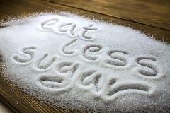 ÄTA MINDRE SOCKER som är skriftligt på högen av socker royaltyfri foto