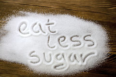 ÄTA MINDRE SOCKER som är skriftligt på högen av socker royaltyfria bilder