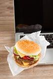 Äta på arbetsstället nära notebbook royaltyfri foto