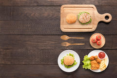 Äta på begreppshamburgare, stekt kyckling, fransmansmåfiskar och tomaten Fotografering för Bildbyråer