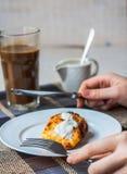 Äta pannkakor för ostmassaost med gräddfil för frukost, händer Royaltyfri Foto
