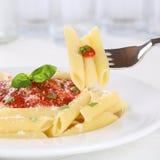 Äta pasta Rigate Napoli med tomatsås med gaffeln royaltyfri bild