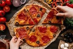 Äta pizza, bästa sikt Händer som tar skivor av varm delisious pizza Pizzaingredienser på trätabellen fotografering för bildbyråer