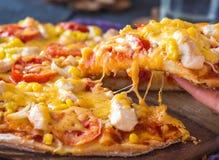 Äta pizza med höna, havre, tomater och ostdubblett, han royaltyfri foto