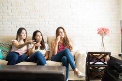 Äta popcorn och hålla ögonen på tv Arkivfoto