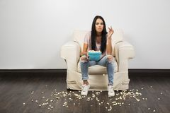 Äta popcorn på en soffa royaltyfri fotografi