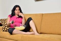 Äta popcorn på soffan - tvfjärrkontroll royaltyfri fotografi
