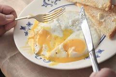 Äta rinnande stekte ägg och rostat brödfrukosten Arkivfoton