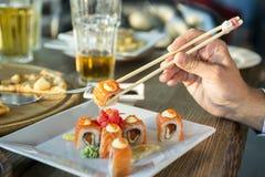 Äta rullsushi i japansk restaurang, hand med pinnecloseupen Fotografering för Bildbyråer
