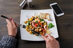 Äta sallad med bläckfisken och grönsaker pov royaltyfri bild